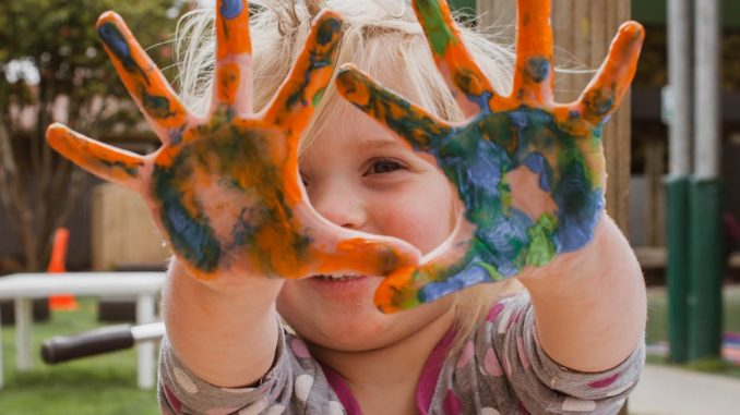 Little young girl with paint in her hands